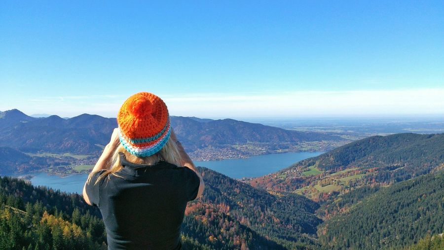 Rear view of woman standing by mountains against sky at tegernsee