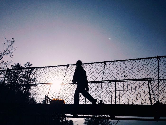 Low Angle View Of Silhouette Man Walking On Footbridge Against Sky