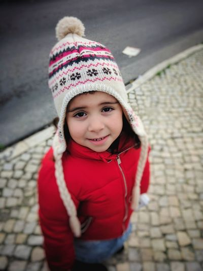 Portrait of cute girl in warm clothing standing on footpath
