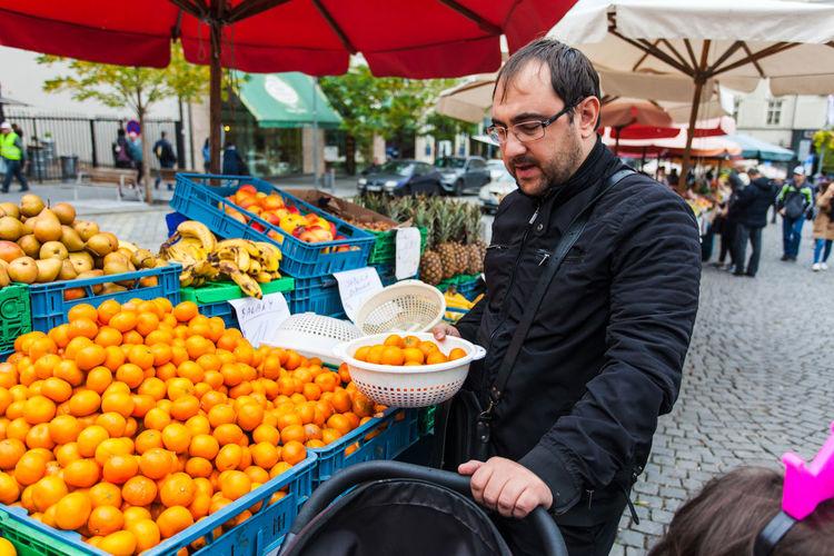 Man holding fruits at market stall