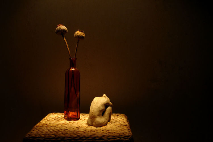 Female Figurine By Flower Vase On Side Table Against Wall