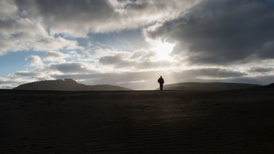 Silhouette man standing on land against sky during sunset