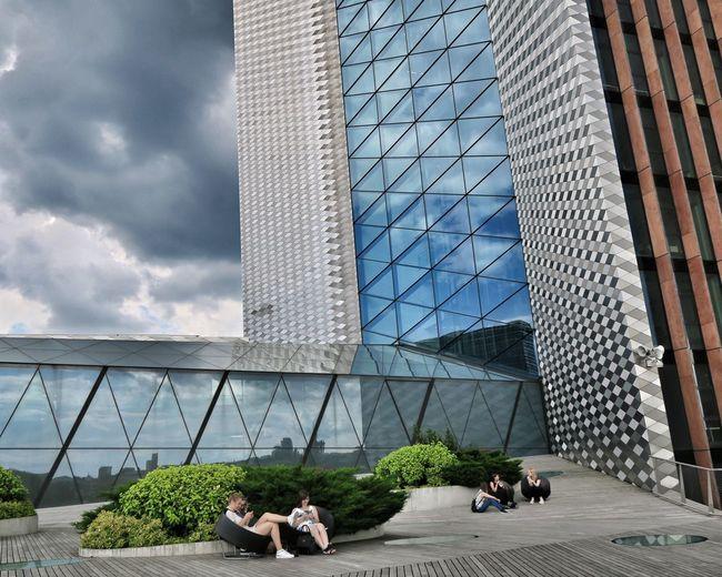 People sitting in modern office building against sky