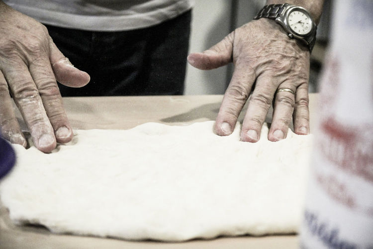 Midsection of man kneading dough in kitchen