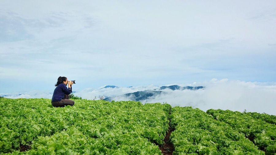 Woman Photographing While Crouching On Agricultural Field Against Sky