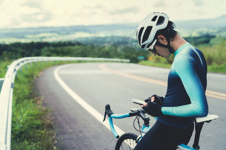 Activity Bicycle Cycling Cycling Helmet Headwear Helmet Land Vehicle Leisure Activity Lifestyles Mode Of Transportation One Person Outdoors Real People Ride Riding Road Side View Sport Sports Clothing Transportation Young Adult