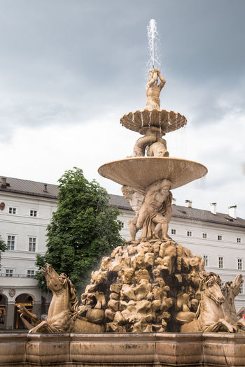 Fountain Against Cloudy Sky In City