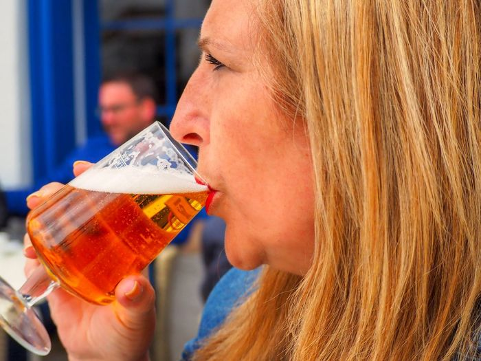 Profile view of woman drinking beer in wineglass