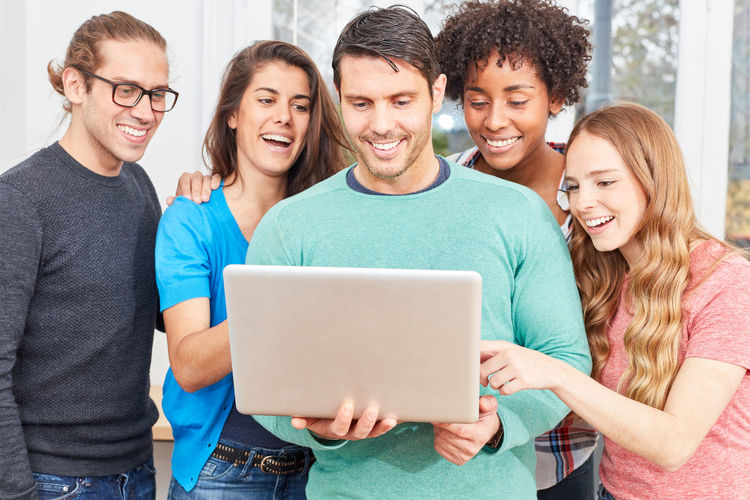 Cheerful business persons looking at laptop at office