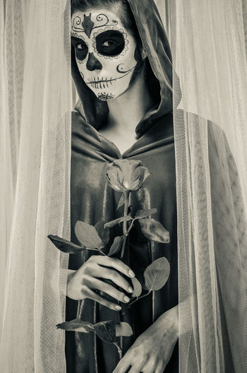 Day of the dead girl with sugar skull make-up Day Of The Dead Death Halloween Horror Makeup Mexican Culture Mortality Woman Black And White Body Arts Day Of The Dead Skull Face Paint Female Flower Girl Holding Hood Macabre Art Mexican Holidays One Person Rosé Skeleton Makeup Sugar Skull Voodoo Young Adult