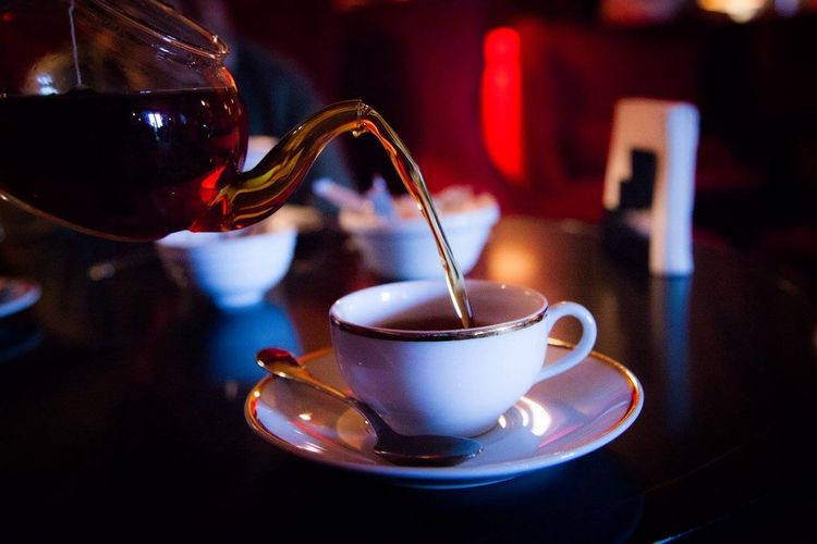 Close-up of tea being poured in cup on table in restaurant