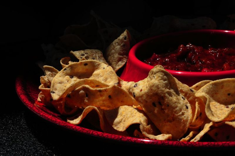 Nachos on a serving dish with sauce Summer Sauce Nachos Chips Food Food And Drink Freshness Still Life Ready-to-eat No People Plate Close-up Red Serving Size High Angle View Bowl Table Meal Wellbeing Black Background Indulgence