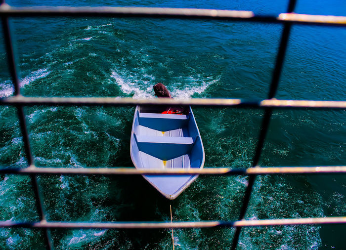 A framing of a boat on blue lake water at kenyir lake, hulu terengganu, malaysia.