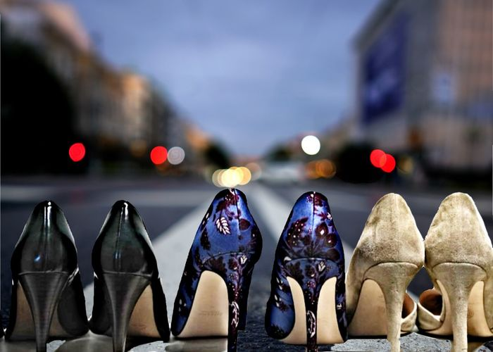Close-up of high heels arranged on road at dusk