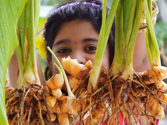 Portrait of girl holding turmeric plant on sunny day