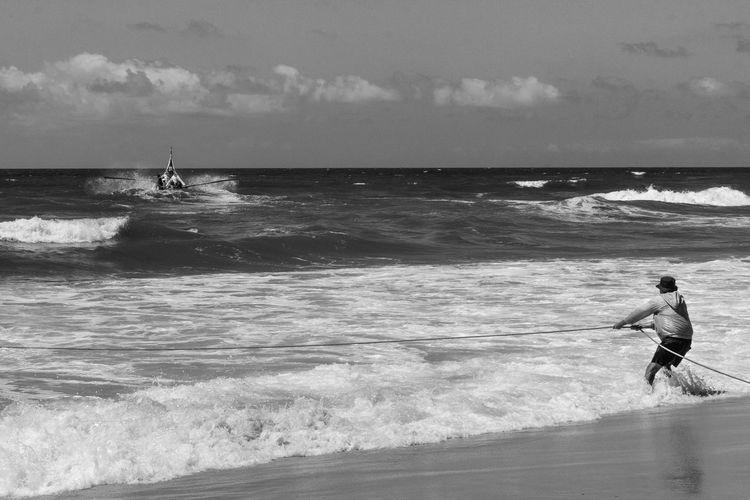 Man pulling rope on beach