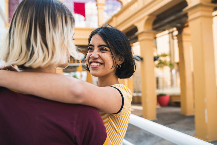 Close-up of lesbian couple romancing while standing in city