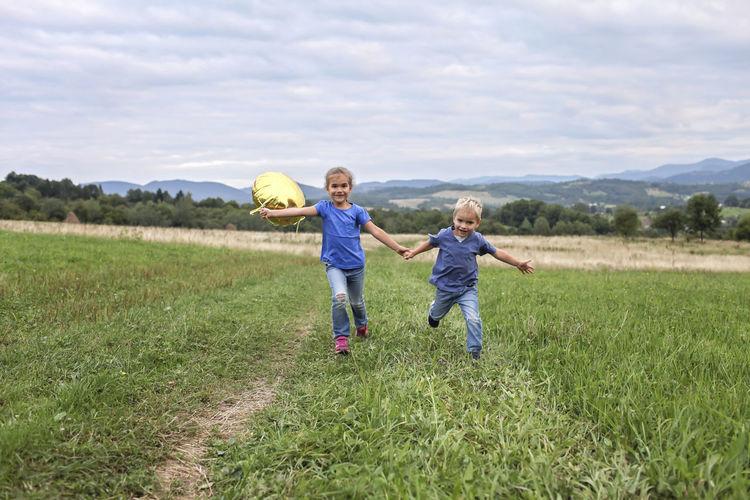 Boy running on grassy field