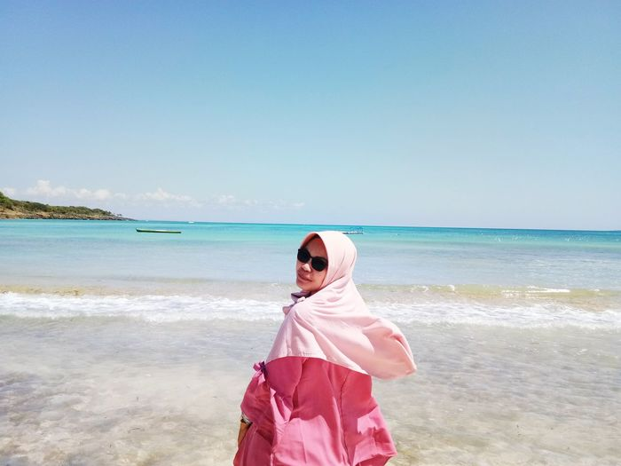 Portrait of woman wearing hijab standing at beach against sky during sunny day