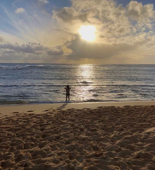 Unrecognizable person, no release needed Hawaii Kauai Silhouette Rear View Woman Snorkeling Sea Beach Sand Horizon Over Water Scenics Water Beauty In Nature Tranquil Scene Shore Sky Sunset One Person Nature Tranquility Full Length Standing Cloud - Sky Silhouette Real People Vacations