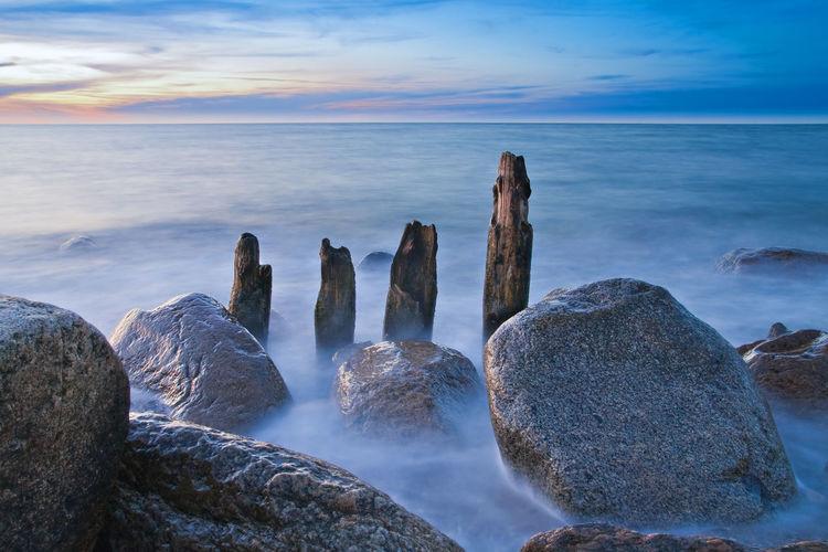 Panoramic shot of rocks in sea against blue sky