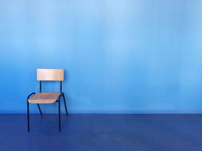Wooden chair in blue corridor Modern Minimalism Chair Blue Seat Copy Space Wall - Building Feature Absence Empty Indoors  Architecture Built Structure No People Sparse Education Wall Building Furniture Business