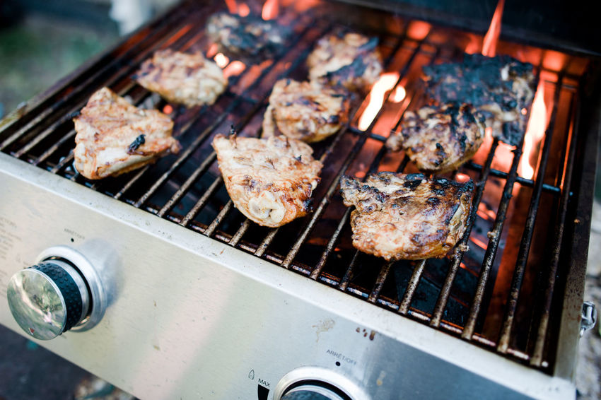 Chicken thighs cooking on a barbecue BBQ Chicken Cooking Barbecue Barbecue Grill Burning Char-grilled Chicken Meat Chicken Thighs Close-up Flame Food Food And Drink Grilled Heat - Temperature High Angle View Meat No People Outdoors Outside Preparation  Preparing Food Summer