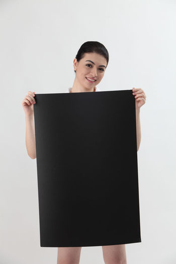 Close up of the woman holding blank card looking at camera Advertisement Advertising Blank Card Cardboard Placard Copy Space Asian  Woman Females Attractive Beautiful Woman Studio Shot White Background One Person Women Indoors  Front View Young Adult Young Women Standing Smiling Holding Communication Happiness Cut Out Portrait Three Quarter Length Looking At Camera