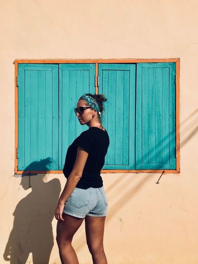 Young woman standing against house during sunny day