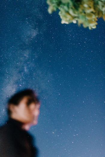 Side view of young man against sky at night