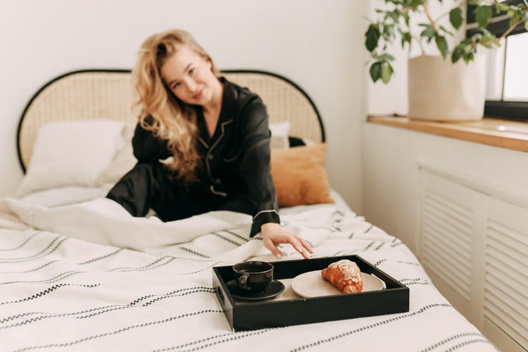 A happy pretty young woman in pajamas is resting and having breakfast in bed in a cozy apartment