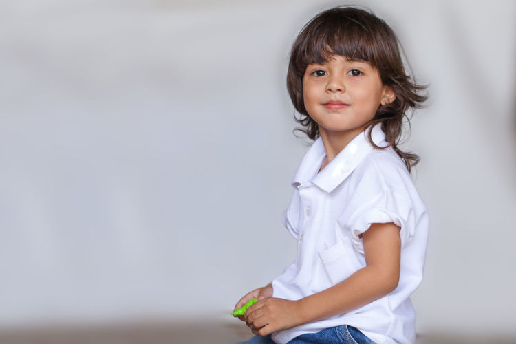 a long hair boy in white shirt and jean playing toy on the ground while waiting for his mom in Mother Day Long Hair, Don't Care. People, Smile, Bangs Boy,  Casual Clothing Child Childhood Cute Females Front View Garland, Girls Hair Hairstyle Indoors  Innocence Looking At Camera Offspring One Person Play, Kids, Family, Fun, Smile Portrait Standing Three Quarter Length Toy, Waist Up Women