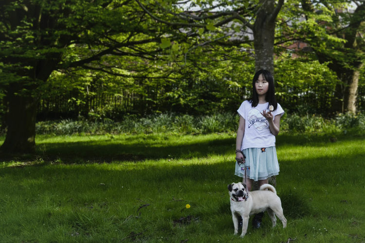 Girl with dog standing on grassy field against trees in park