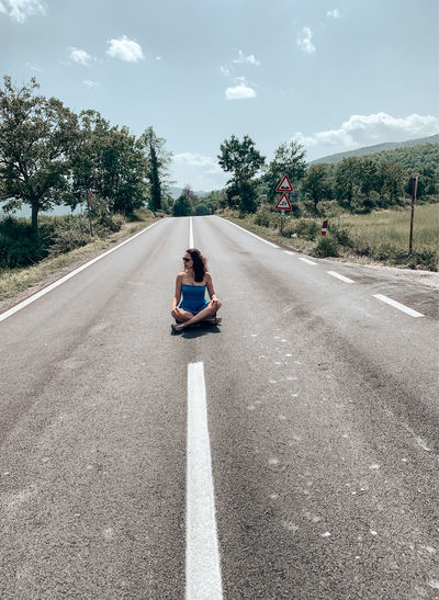 Full length of woman sitting on road against sky