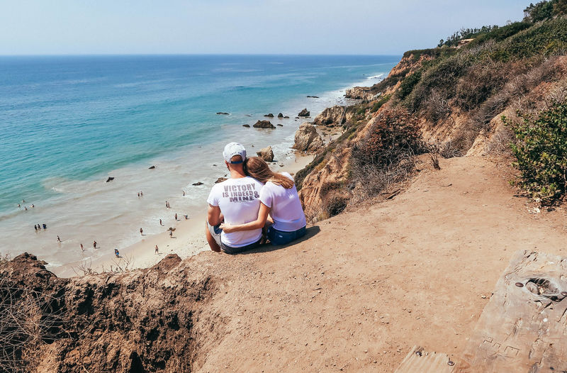 High Angle View Of Couple Sitting On Cliff Against Sea