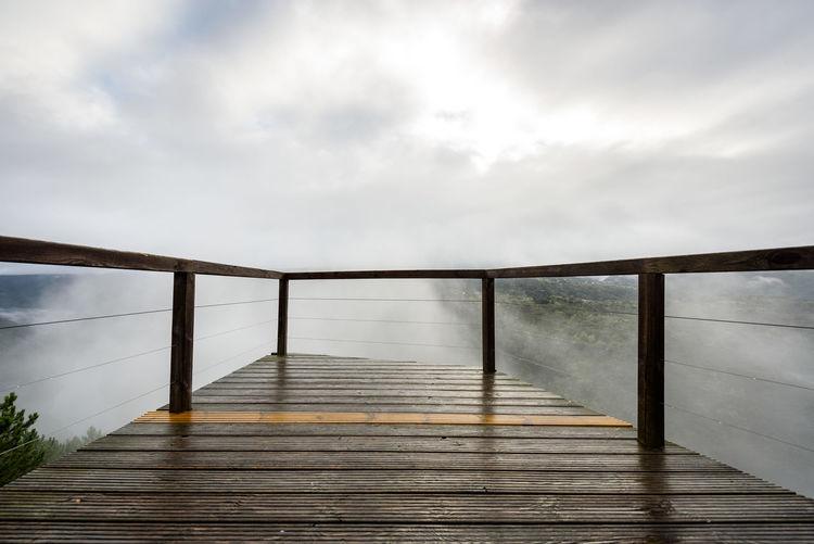Footbridge over footpath against sky