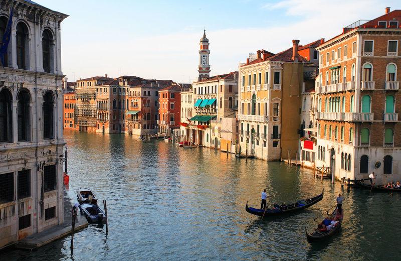 Gondolas on grand canal amidst buildings against sky