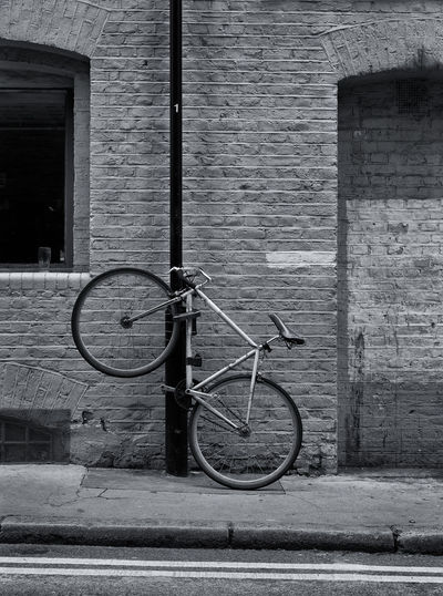 Bicycle parked against wall in old building