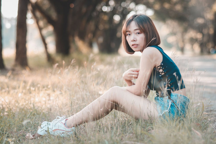 Asian Girl Asian Teen Beautiful Woman Casual Clothing Full Length Grass Hairstyle Innocence Land Lifestyles Nature One Person Outdoors Portrait Real People Side View Sitting Tree Young Adult