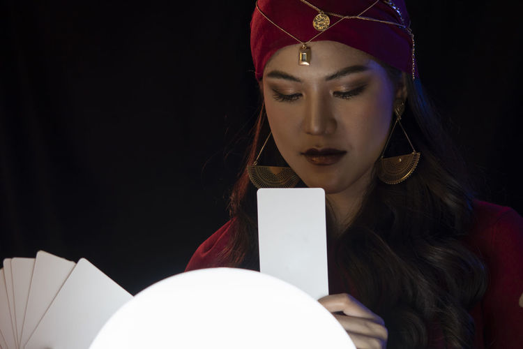 Female fortune teller looking at tarot card against black background
