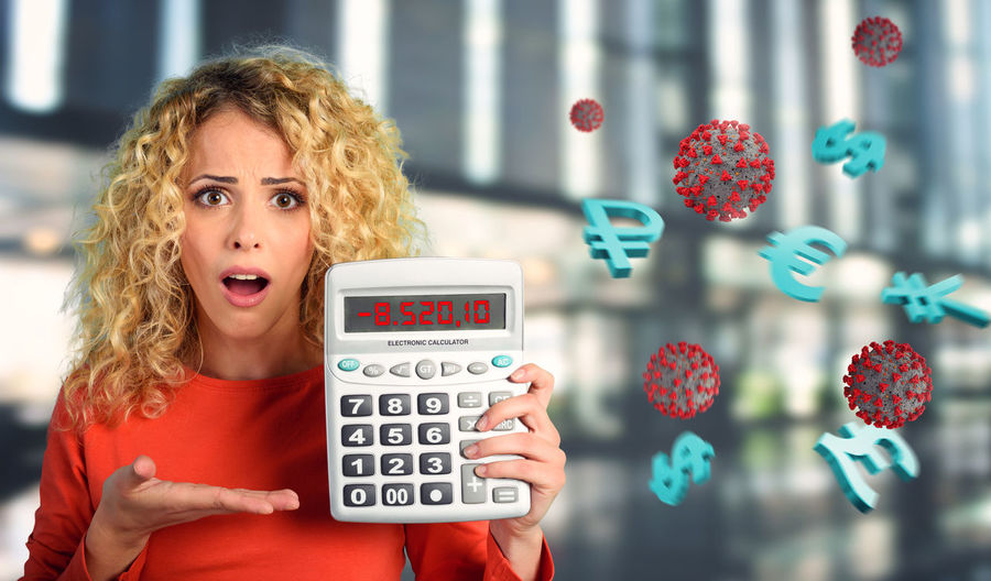 Digital composite image of woman holding calculator by currency symbol and virus