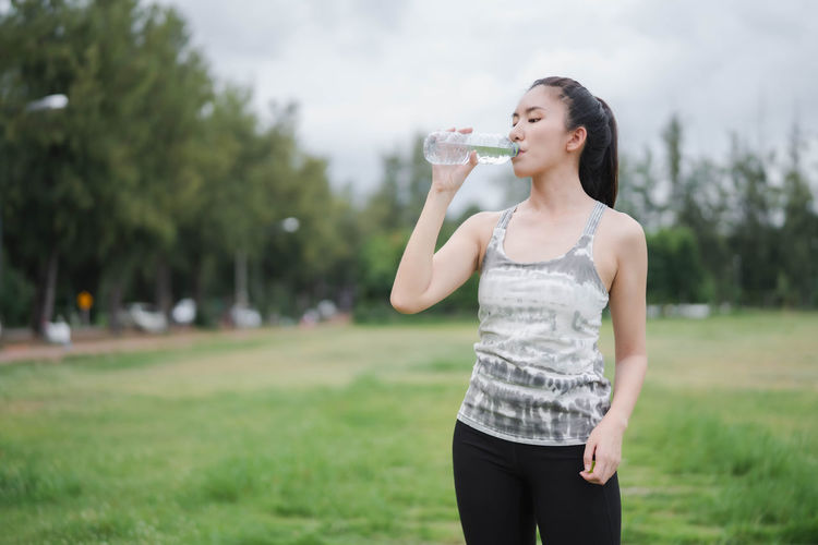 Full length of a beautiful young woman drinking water