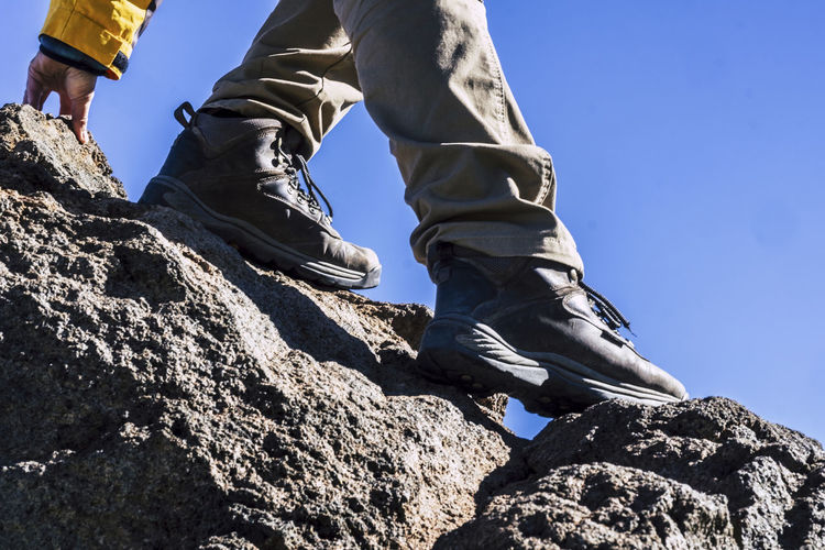 Close up of hiker legs and shoes rocking the mountain helping with one hand - concept of outdoor leisure activity and sport lifestyle - adventure and difficult enjoying the open air Human Leg Low Section Body Part Solid Real People Sky Rock Lifestyles Shoe Low Angle View Human Body Part Nature Leisure Activity Rock - Object Men Day One Person Climbing Adventure Outdoors Human Foot Human Limb Hiker Volcanic Rock Mountain Help Sport Enjoying The Nature Blue Sky Morning Springtime Casual Clothing Caucasian Difficult Vacations Tourist Man Males  Adversity Vitality