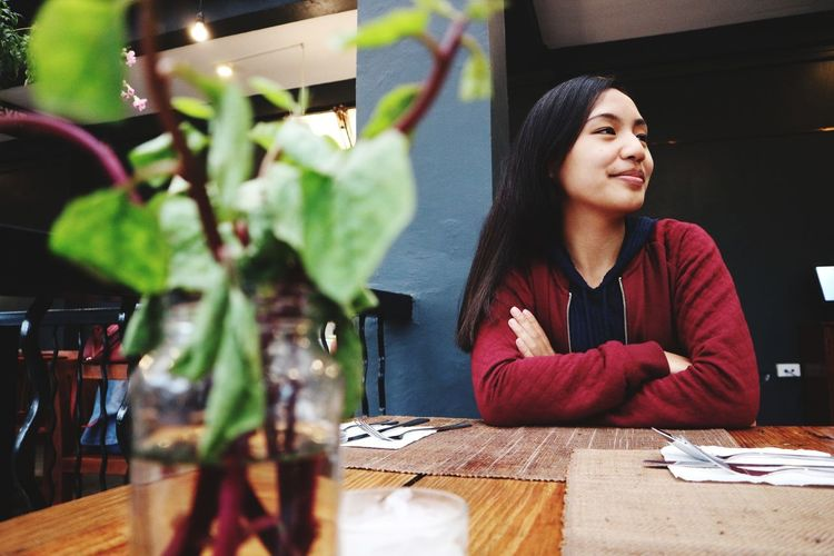 Thoughtful young woman sitting at table in restaurant