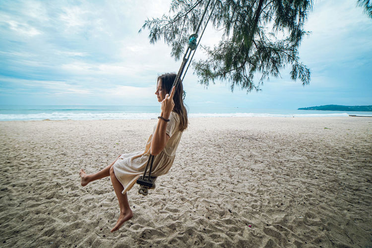 Side view of young woman swinging  on beach