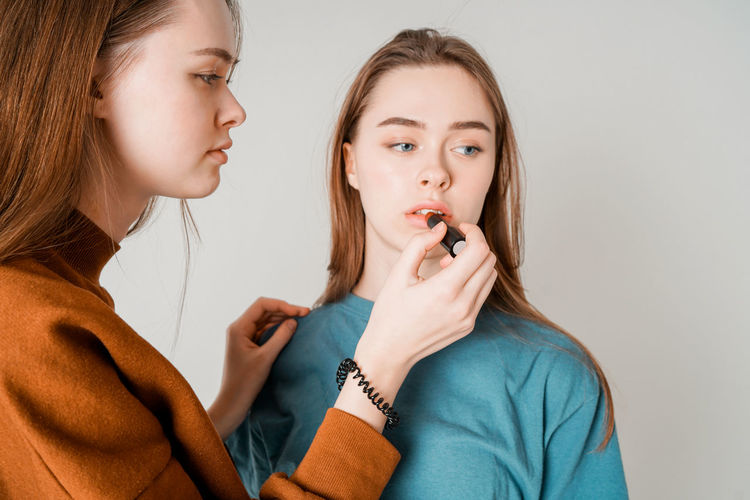 Two sisters twins beautiful girls in casual painting lips doing make up on grey background isolated Two People Women Indoors  Child Togetherness Girls Casual Clothing Headshot Portrait Teenager Females Young Women Young Adult Teenage Girls Holding Looking Childhood Family Adult Sister Hair Hairstyle