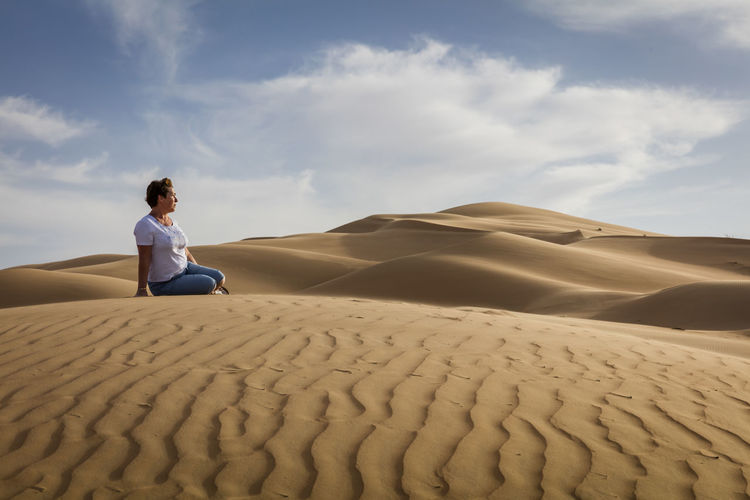 Man sitting on sand dune in desert against sky