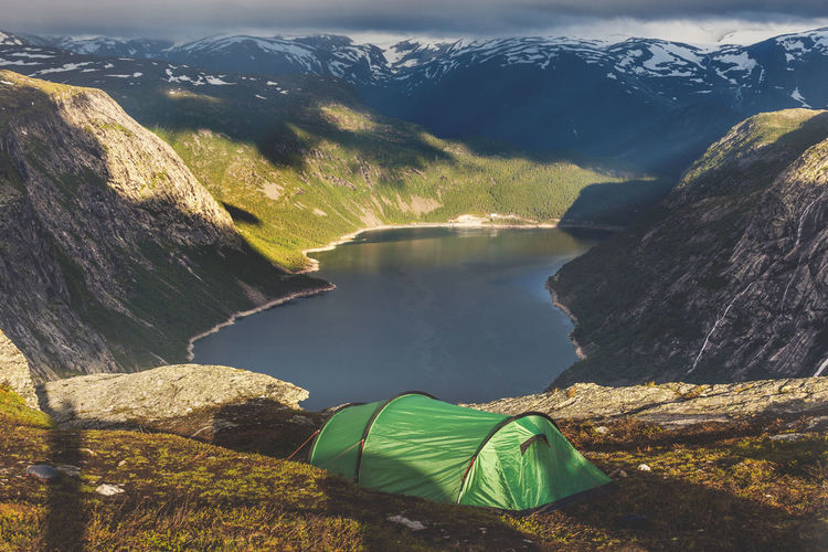 Tourist's tent in the mountains near  troll tongue rock. trolltunga. sunrise above fjord, norway.
