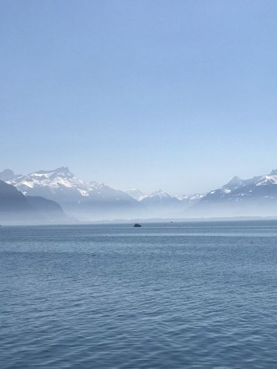 Scenic view of sea and snowcapped mountains against sky