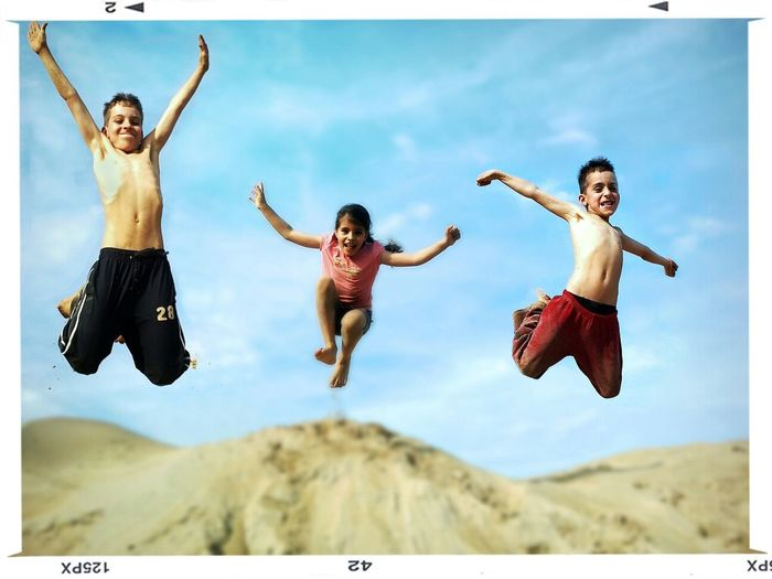 Portrait of cheerful siblings jumping on sand against blue sky